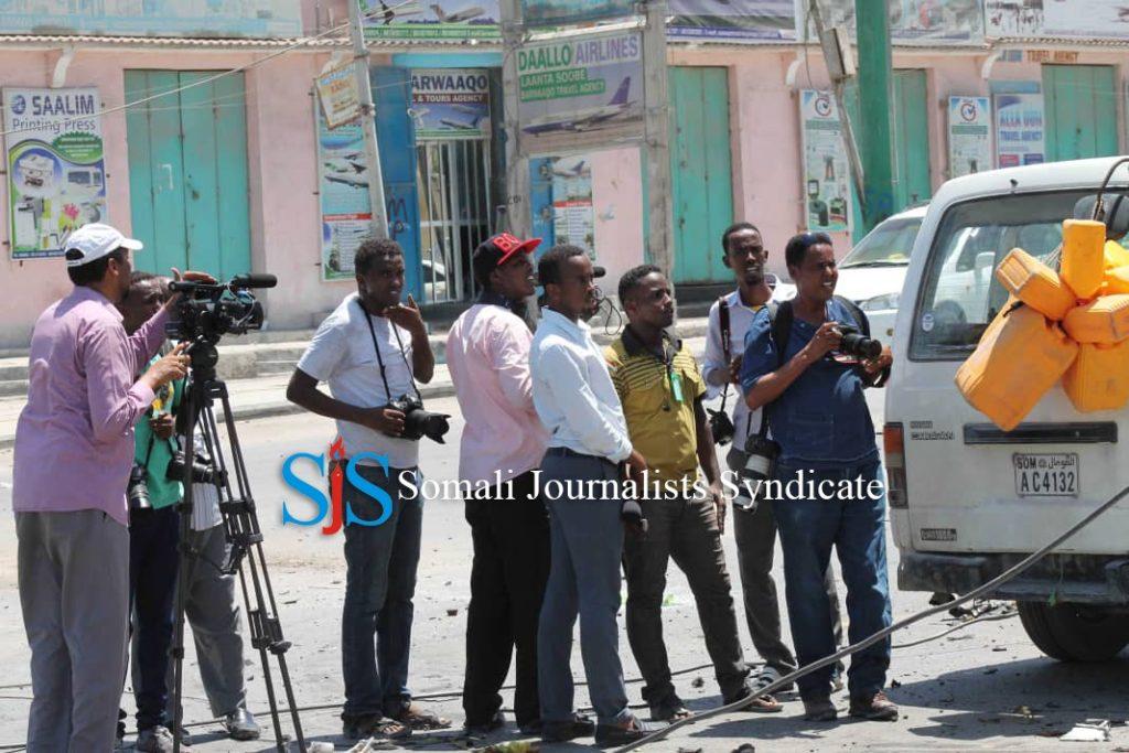 Journalists stand near a blast site in Mogadishu. | PHOTO CREDIT/SJS.